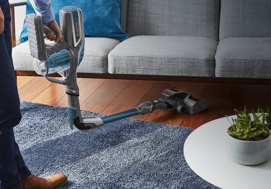 Man vacuuming under a sofa