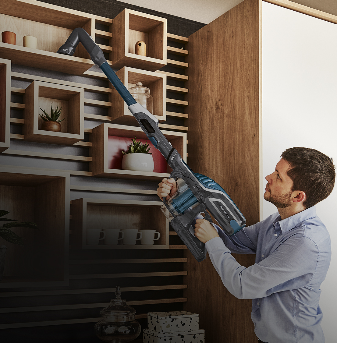 Man vacuuming dust on a furniture