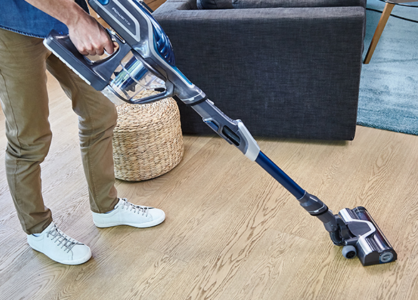 Man vacuuming dust on the floor